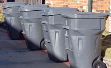 trashcans lined up along a sidewalk
